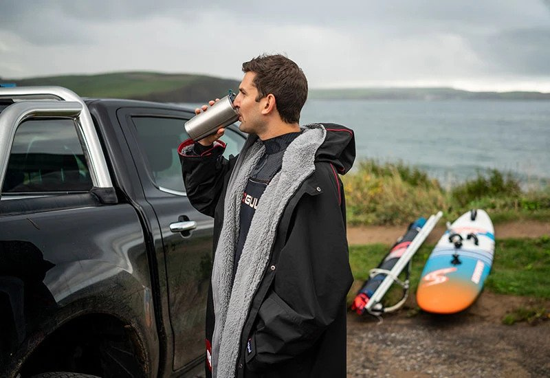 Man Standing next to his black truck while drinking from Insulated Cup and wearing a black waterproof changing robe