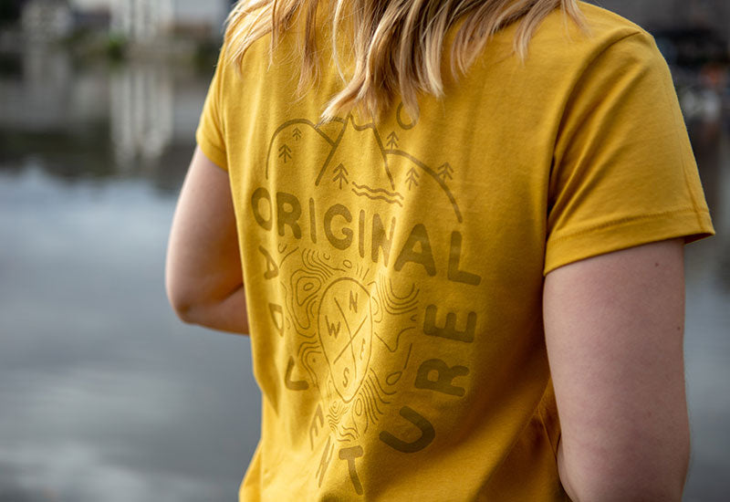 Woman Wearing Mustard Yellow Red Original Adventure Womens T-Shirt close up of logo on back