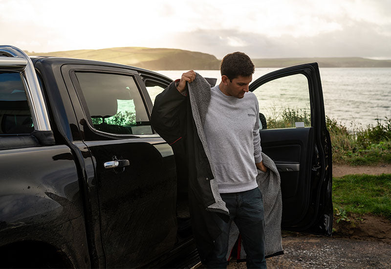 Red Original Men's Long Sleeve Pro Change Robe - Black with Grey Lining being put on in a car park