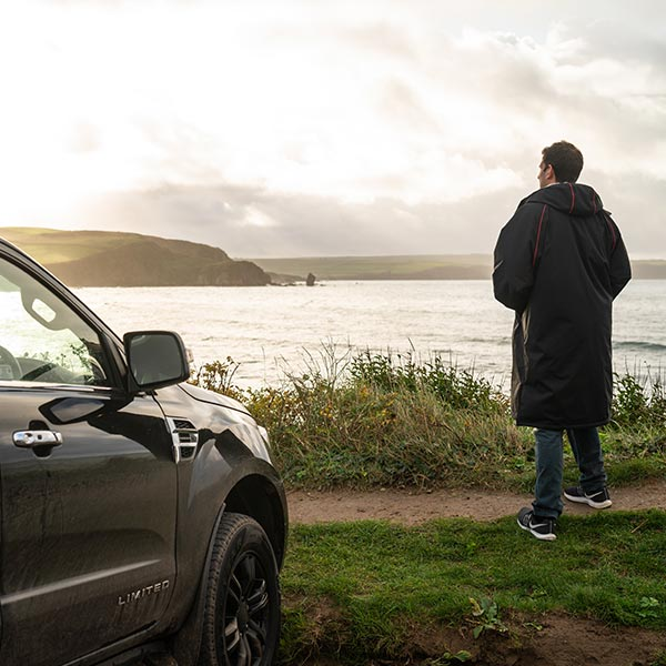 Man standing by a car looking out over the sea