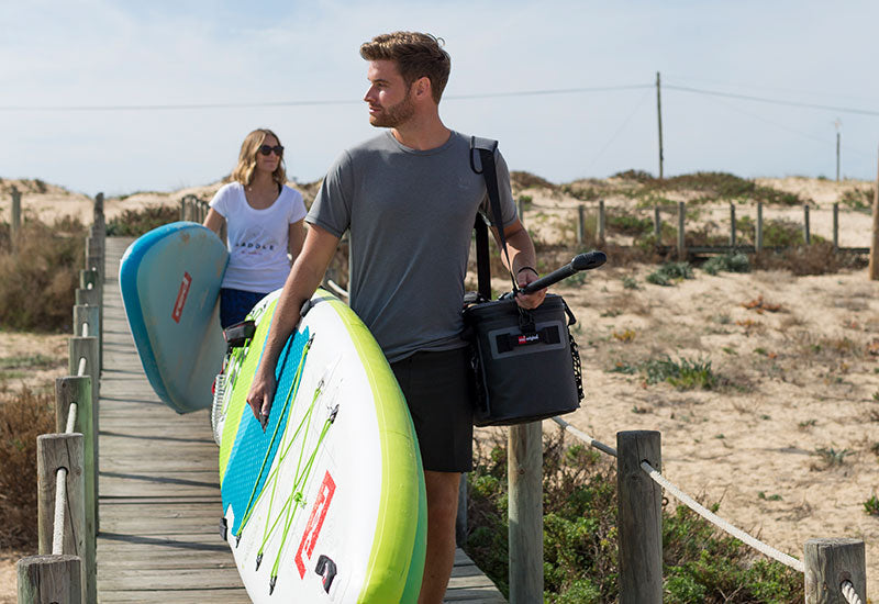Couple carrying paddle boards with the woman wearing the Red Original paddle on t-shirt