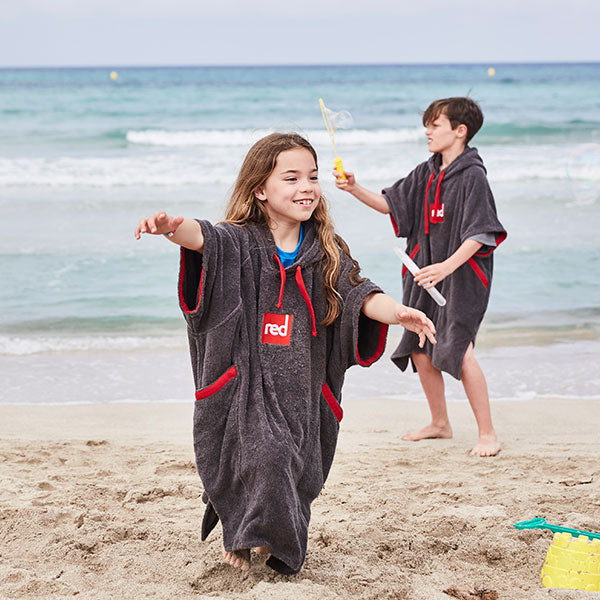 Girl and Boy playing on the beach wearing a towelling robe