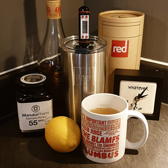 Hot Toddy In An Insulated Travel Cup Surrounded By Ingredients