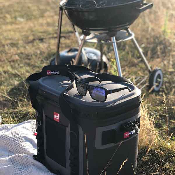 The Red Original Cooler Bag Next To A BBQ