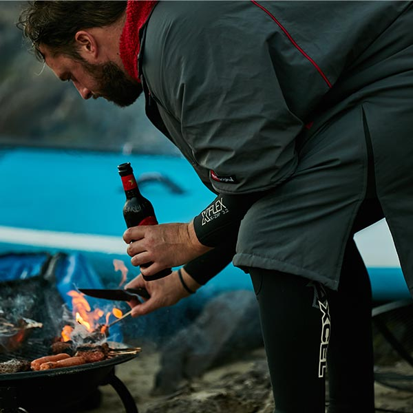 Man wearing a wetsuit and Pro change robe turning sausages over on a BBQ while drinking a beer