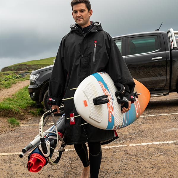 Man with a surf board walking away from a car on an overcast day
