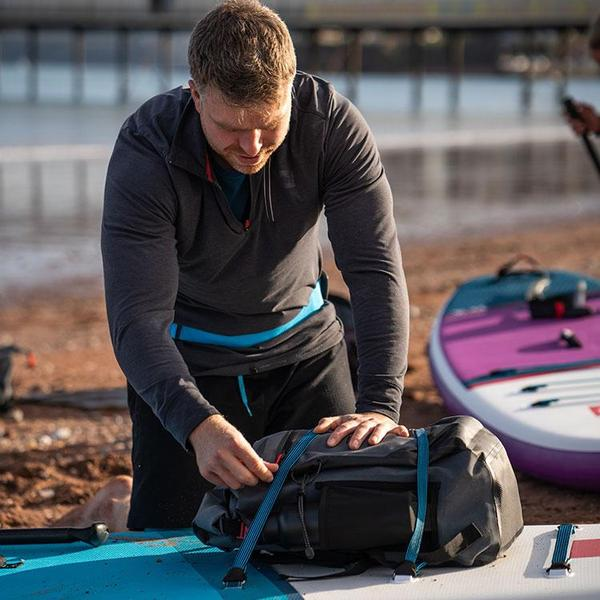 Man strapping waterproof backpack onto a paddle board