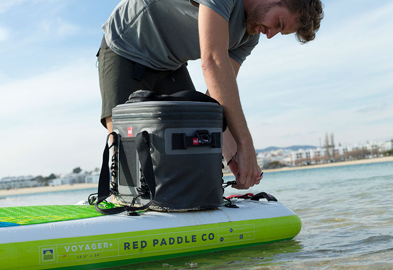 Red Original Waterproof Cooler Bag Being Attached To A Red Paddle Board