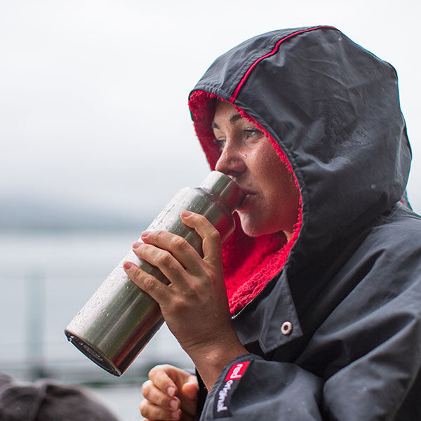 Woman Wearing the Pro Change Robe With Hood Up Drinking from an Insulated Water Bottle