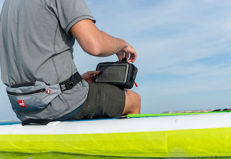 A Man Sitting On His Red Paddle Board While Opening The Waterproof Pouch