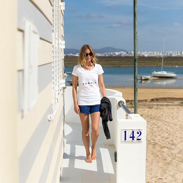 Woman Wearing White Red Paddle Co Women's T-Shirt Walking To The Beach
