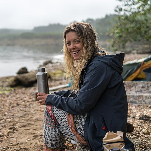 Woman wearing the Red Original Waterproof Active Jacket sat on a camping chair
