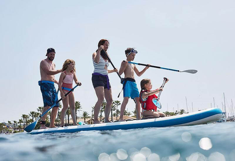 Kids and adults out on a paddle board