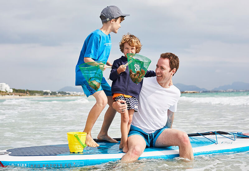 Kids with their dad on a paddle board