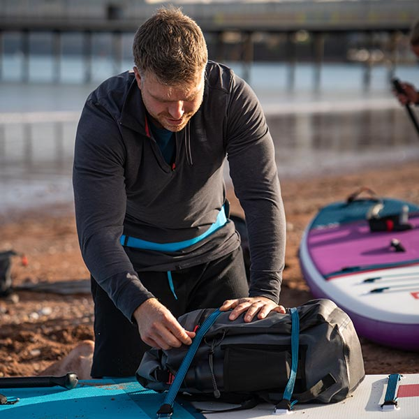 Waterproof Backpack being strapped to a Red Paddle Board
