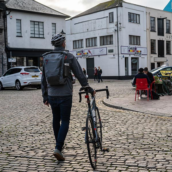 Cyclist wearing the Red Original Waterproof Backpack on The Plymouth Barbican
