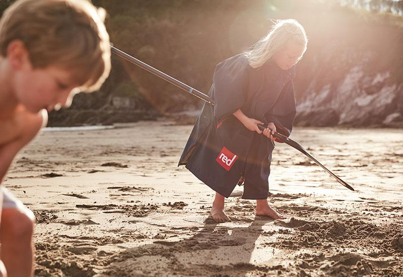Girl wearing kids changing robe digging with a paddle