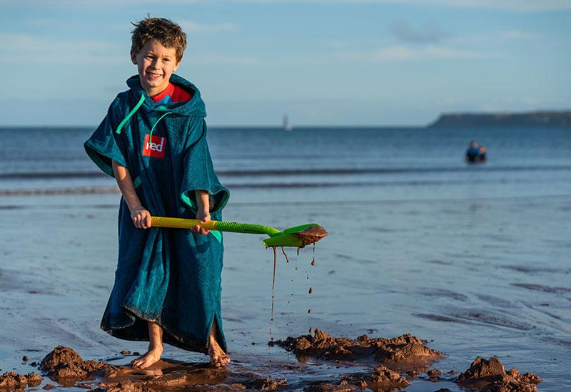 Boy wearing a poncho towel digging on the beach with a spade