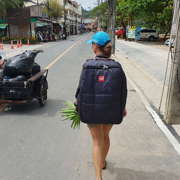 Woman walking down the street with a Red Paddle Co Paddle Board