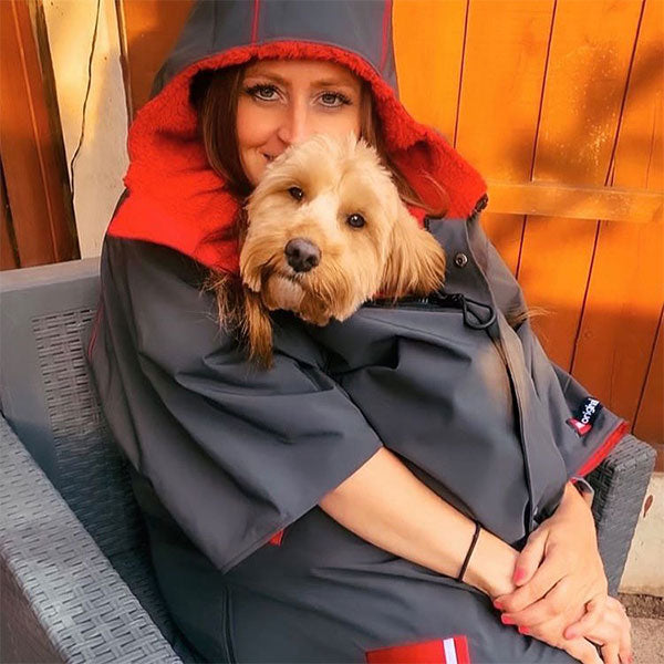 Woman wearing a changing robe with her dog inside