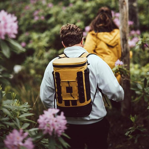 Woman walking through a forest carrying a Mustard Cooler Backpack