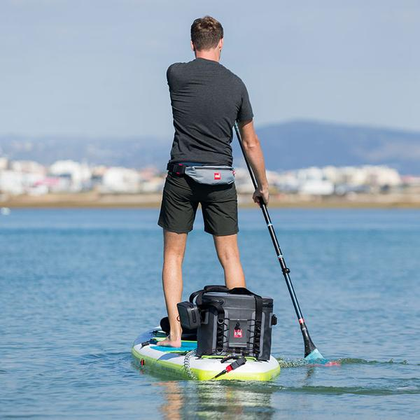 Man on a paddle board with a cooler bag strapped to the back