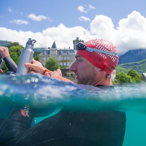 Man swimming in a lake and drinking from a reusable water bottle