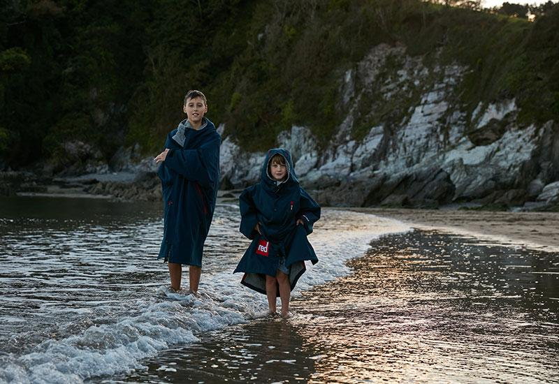 2 boys standing in the sea wearing a changing robe