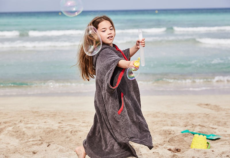 girl blowing bubbles on beach in red original luxury robe