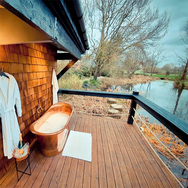 A relaxing nature retreat with a balcony and a bath tub
