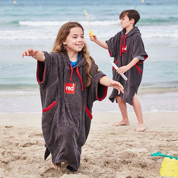 Boy and Girl on a beach Wearing Red Original Towel Changing Robe For Kids in Grey