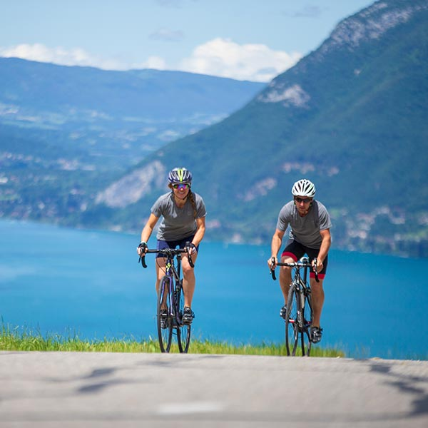 Man and Woman Cycling uphill on a sunny day