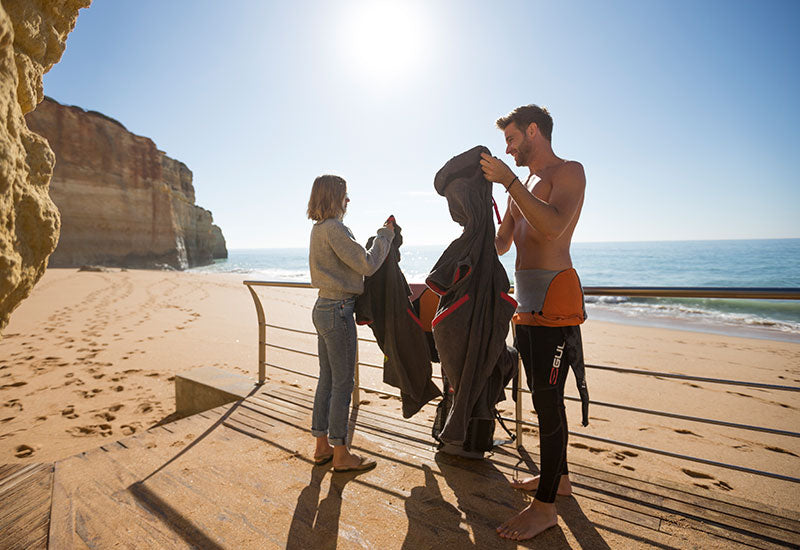 Couple about to get changed at the beach with their Red Original Luxury Changing Robes