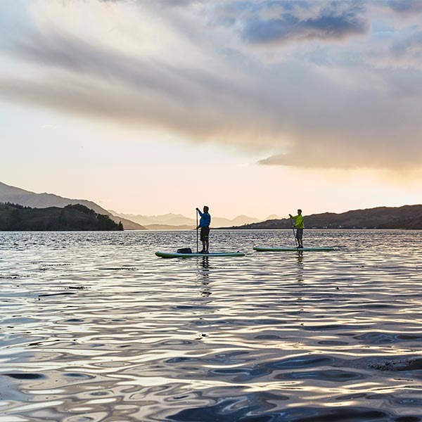 2 people paddle boarding on a lake