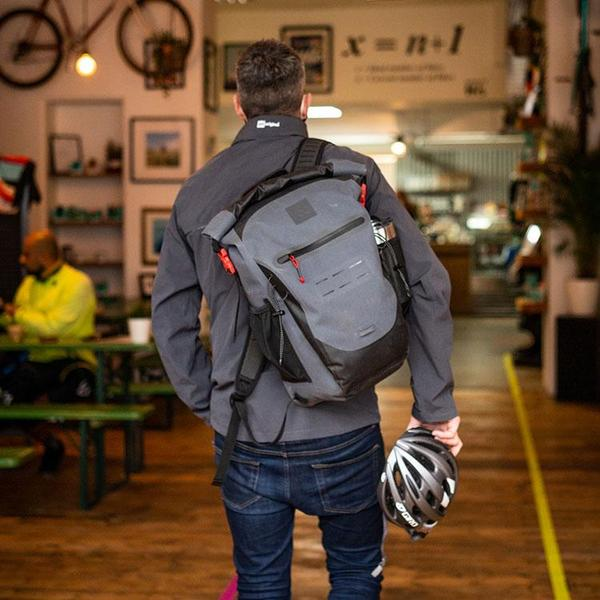 Cyclist walking into a cafe carrying a cycling helmet and carrying a bag