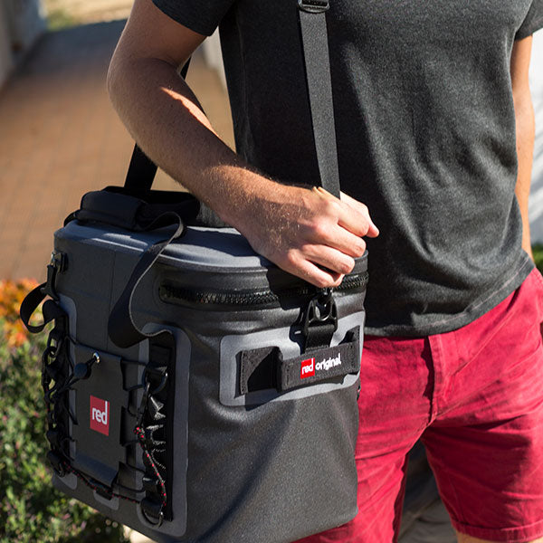Man Carrying The Red Original Waterproof Insulated Bag With A Shoulder Strap