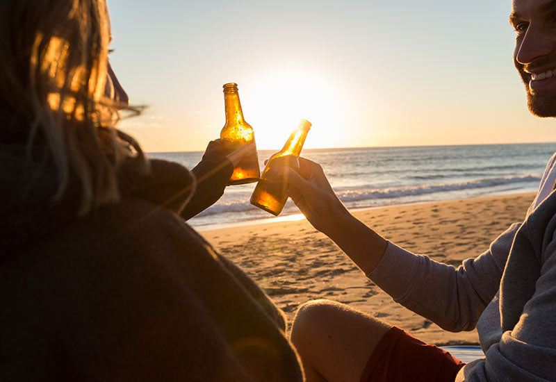 people enjoying beers at sunset on beach