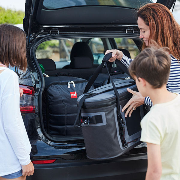 Family loading the car with paddle boards and cooler bag