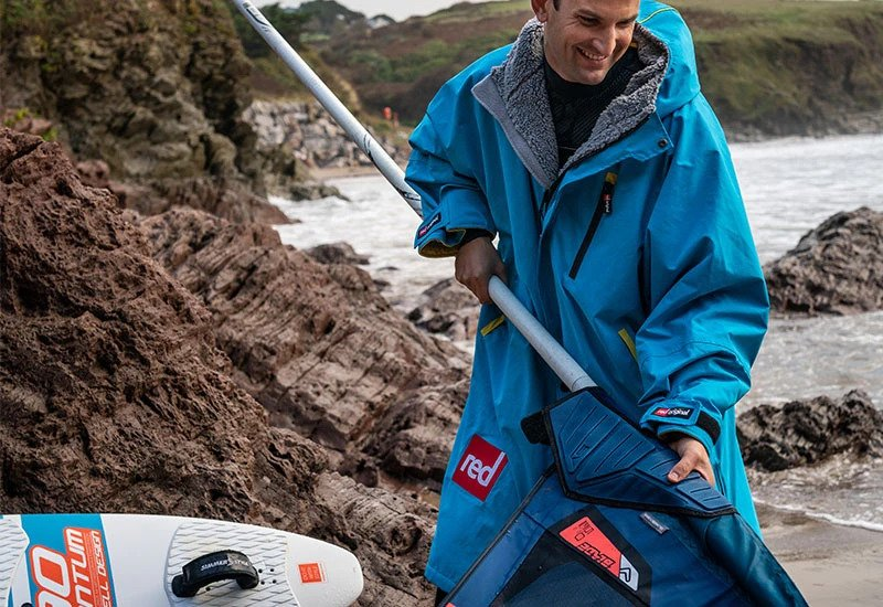 Man wearing blue changing robe pulling paddle board paddle from a paddle bag