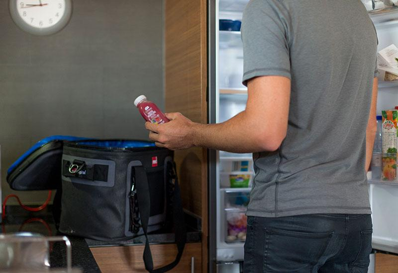 Man filling waterproof cooler bag with contents from the fridge