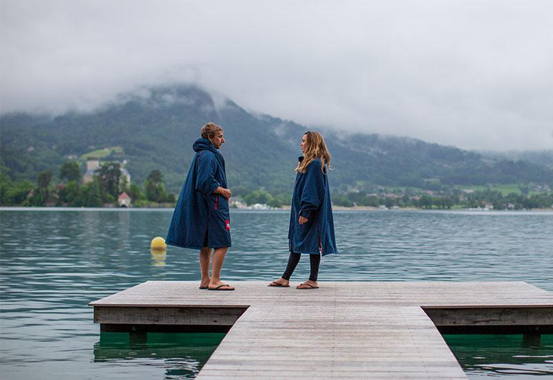 Man and woman wearing waterproof changing robes standing on a jetty