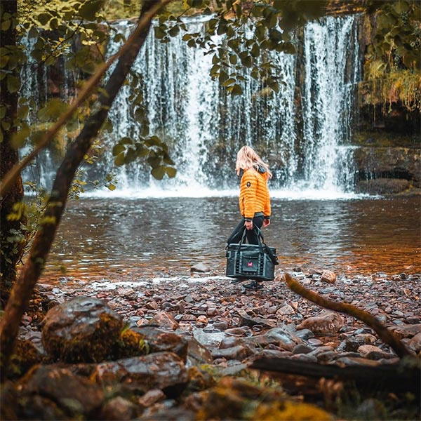 Woman carrying waterproof cooler bag by a waterfall