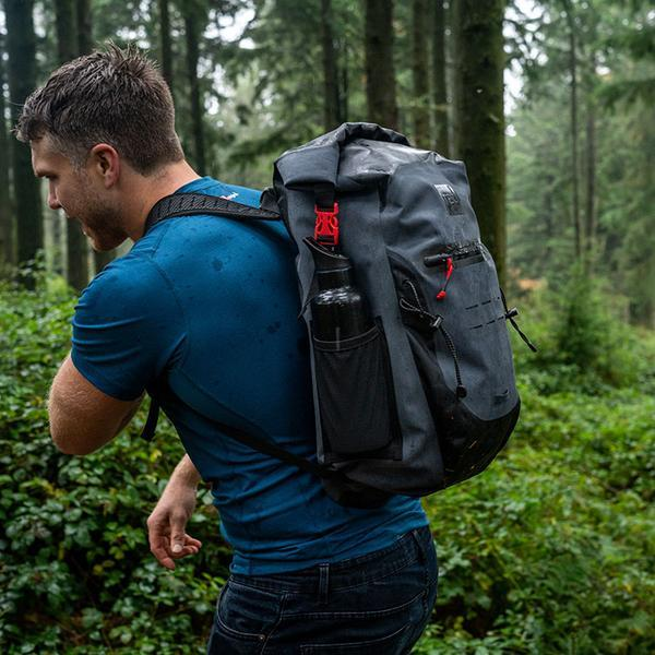 Man walking through a forest with a waterproof backpack