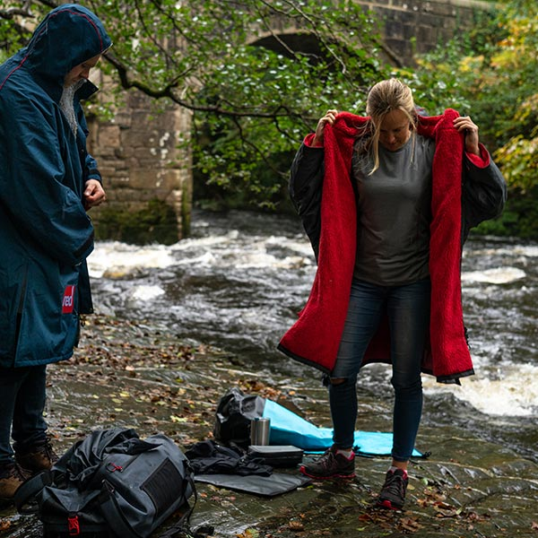 2 women on a river bank putting changing robes on