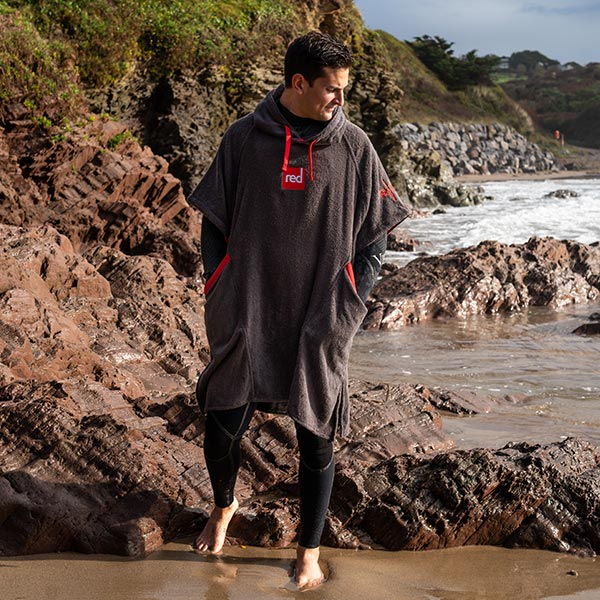 Man on beach in a wetsuit and towelling robe