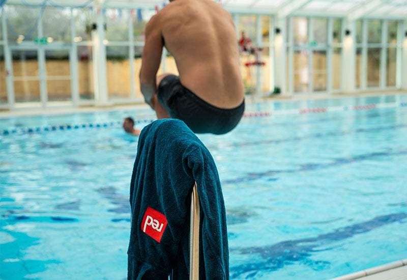 man bombing in the pool with Red Original Men's Luxury Towelling Robe - Navy on the railing
