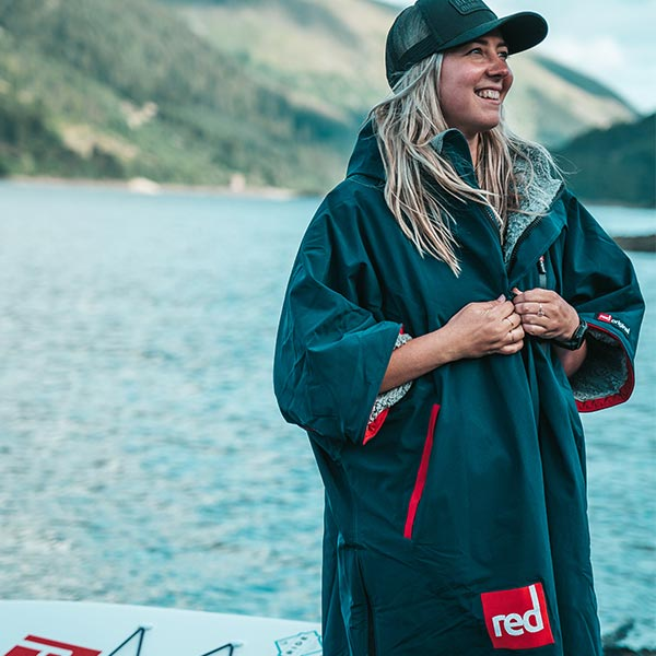 Woman standing on a river bank with her paddle board wearing a Pro change robe
