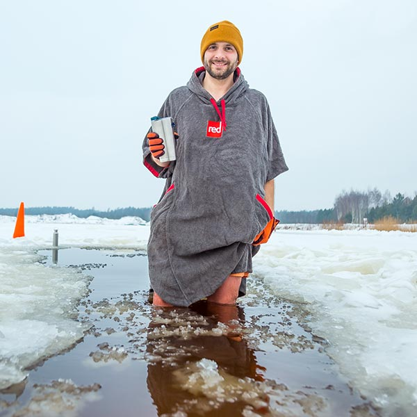 Man standing in icy water wearing a grey coloured Red Original towelling robe and orange hat while holding an insulated cup