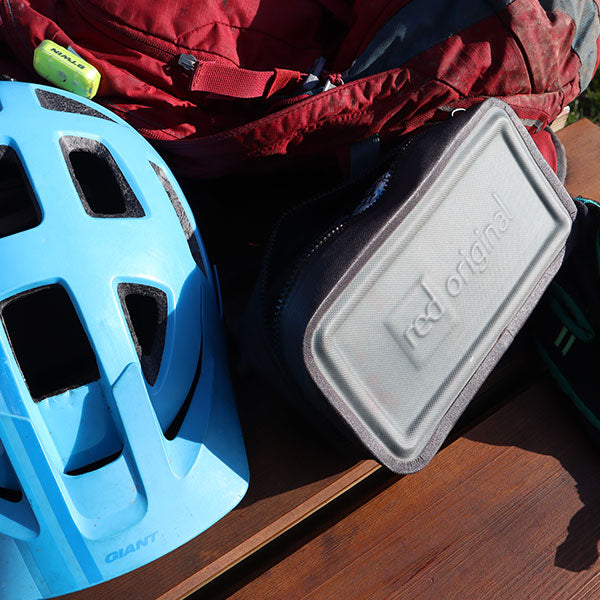 The Waterproof Pouch next to a safety helmet