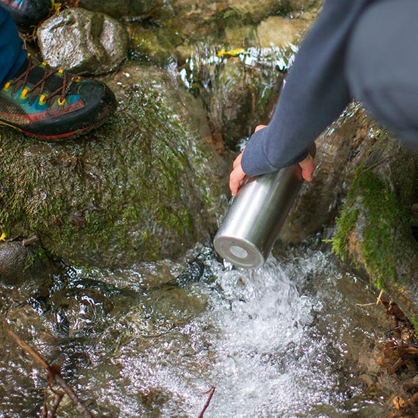 Woman Filling Up A Reusable water bottle from a stream